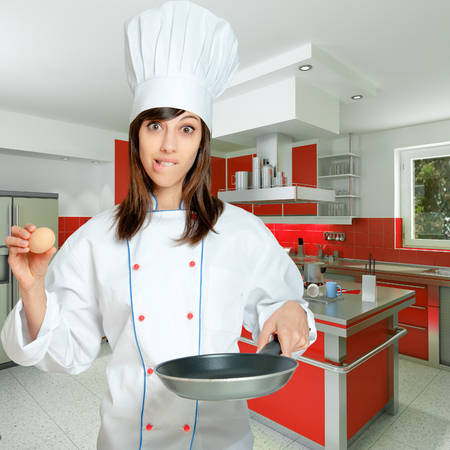 countertop:  Young woman in chef�s  attire with funny expression with an egg and a frying pan   Stock Photo