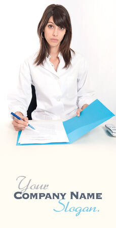 admissions:   Serious young woman in a lab coat sitting at the desk  with an open folder   Stock Photo