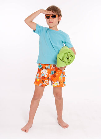 Little boy in swimming trunks with a rolled up beach towel and sunglasses