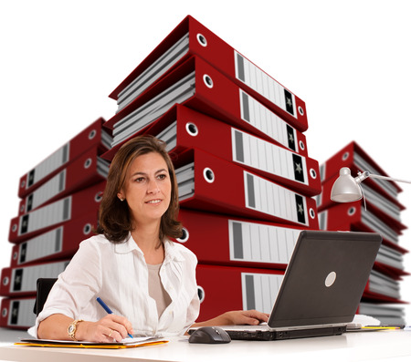 Woman sitting at her desk with piles of ring  Stock Photo