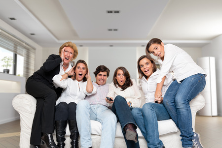 A group of family members sitting at home watching nervously a match   photo