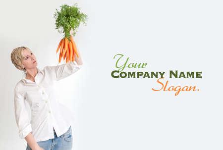 slogan: Retrato de una mujer que sostiene un manojo de zanahorias Foto de archivo