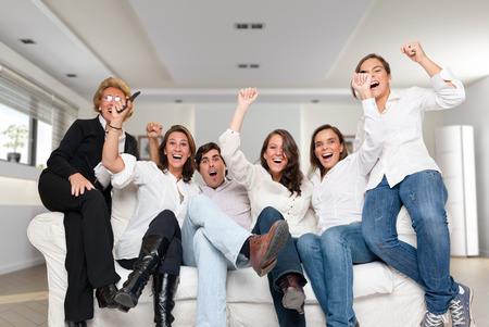 A group of family members sitting at home cheering   photo