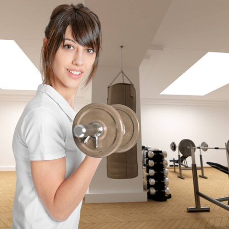 conscious:   Young woman in a gym lifting a dumbbell