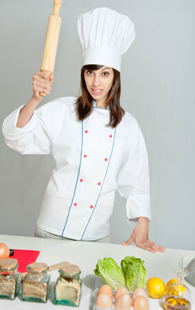 Young woman in a chef�s attire holding a rolling pin with a menacing expression   photo