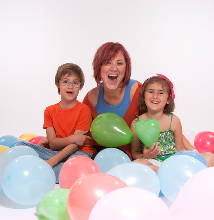 Mom with boy and girl playing with colourful balloons photo