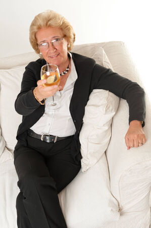 black pants: Attractive elegant senior lady holding a glass of white wine on a toast Stock Photo