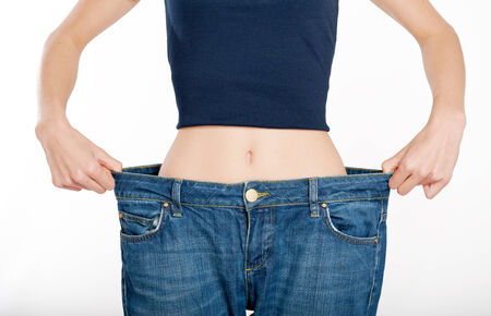 weight loss success:  Successful weight loss, woman with too large jeans after a diet  Stock Photo