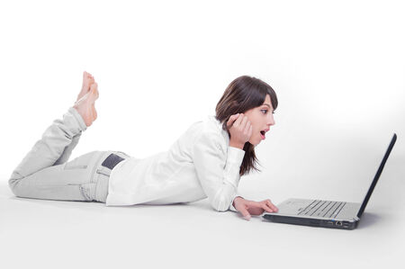 telecommuting:   Young woman using a laptop computer on the floor    Stock Photo