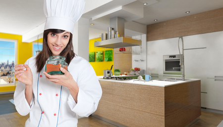 countertop:  Young female chef in a kitchen interior with a glass jar with red chilly powder