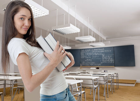 Portrait of a girl in a maths classroom carrying two big books   photo