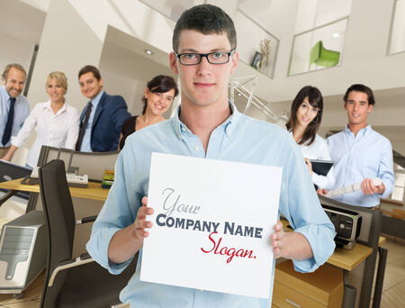 Young man holding a blank sign in an office with a supporting team photo