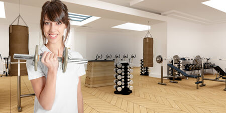 athleticism:   Young woman in a gym lifting a dumbbell