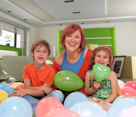 Mother and kids surrounded by balloons in a home interior  photo