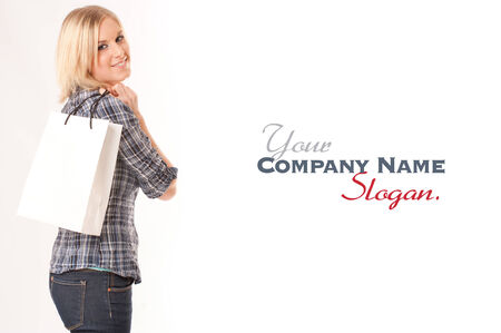 Young blond woman happily holding a shopping bag against a white background  photo