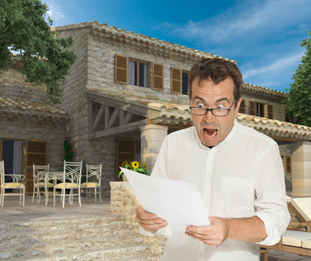 Horrified man reading a document by a magnificent house photo