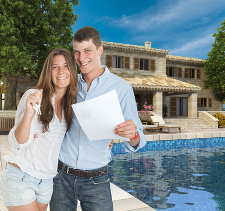 Young couple by a beautiful house with swimming pool holding a document and a bunch of keys photo