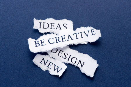 Roughly cut slips of paper with creativity concepts such as ideas, be creative, design, new photo