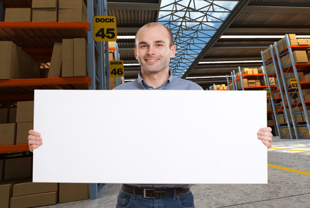 A man holding a blank board in a distribution warehouse, ideal for inserting your own message photo