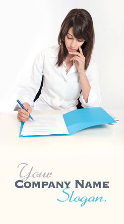 Serious young woman in a lab coat sitting at the desk  with an open folder   Stock Photo