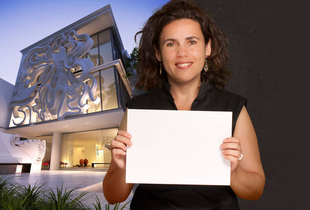 Woman holding a blank paper by an elegant building, ideal for customization
