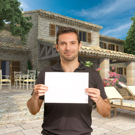 Man holding a blank, customizable message by a beautiful house photo