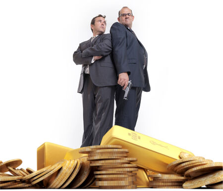 Man with gun and scared businessman with a pile of gold Stock Photo - 27203652