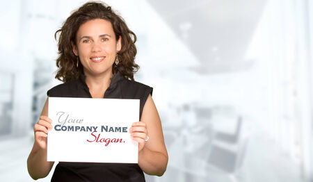 company premises: Picture of a woman holding a blank sign on a business background Stock Photo