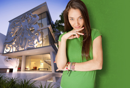 Young woman standing by an elegant contemporary building with an original sculpture in the fa�ade photo