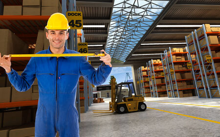 Worker with tape measure in a distribution warehouse photo