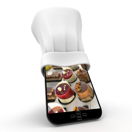 Tablet wearing a chefs toque with the picture of delicious cakes photo