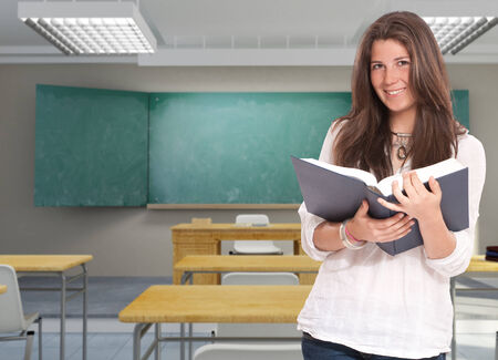 cute girl with long hair: Smiling young girl holding an open book in a classroom