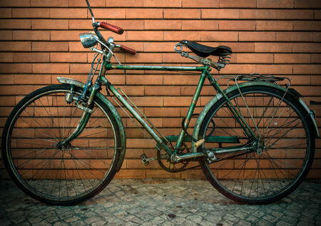 battered: Vintage bicycle against a brick wall