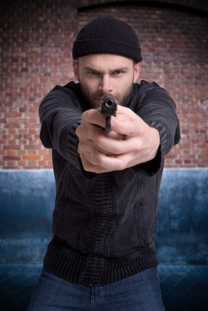 Man pointing a gun with a brik wall photo