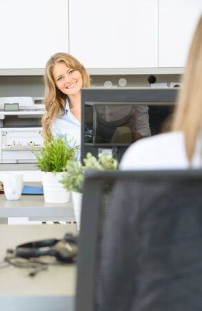 Happy woman at her desk, in front of coworker photo