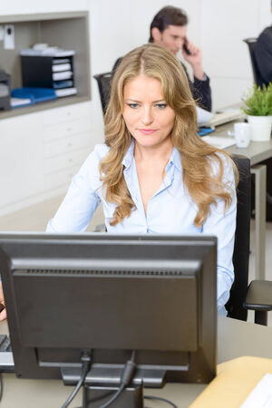 Woman working at her desk, with people working at the background photo