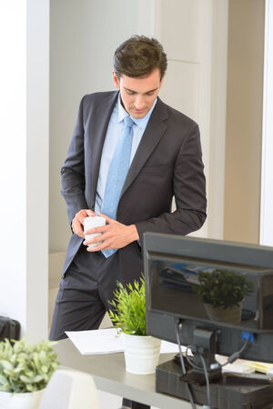 Businessman standing with a coffee, reading a document photo