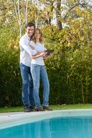 latin man: Romantic couple looking at a digital tablet standing by the pool Stock Photo