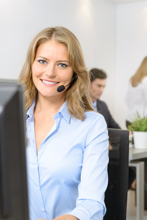 Attractive smiling woman at her desk with handset with people working at the background Stock Photo