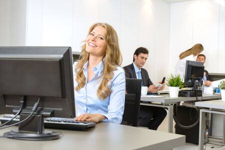 corporate women: Happy businesswoman at her desk, with people working at the background Stock Photo
