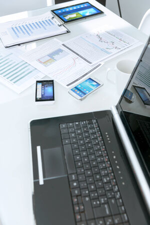 Office table with laptop, tablets, smartphones, coffee cup,  and documents with charts photo