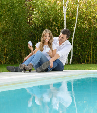 Couple sitting by the pool with the girl opening a gift box photo