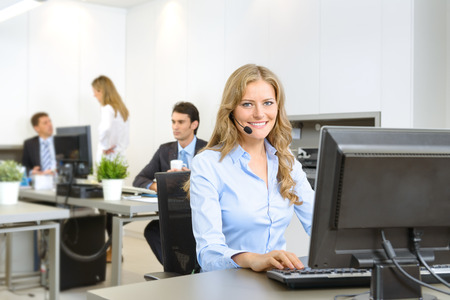 Attractive smiling woman at her desk with handset with people working at the background Zdjęcie Seryjne