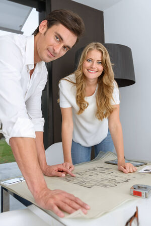 Man and woman looking at unrolled blueprints photo
