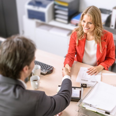 Male and female business people shaking hands