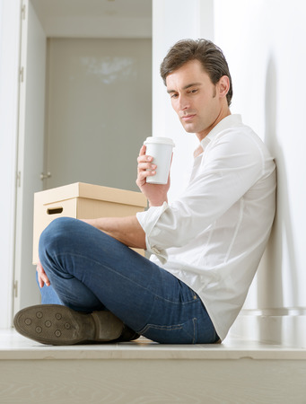Man with a pensive expression, having a coffee on the floor with a pile of boxes close by photo