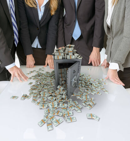 safety deposit box: businesspeople around a table with a safe and piles of cash