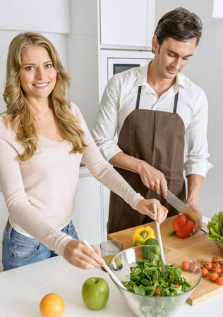 Couple preparing a healthy meal with fresh vegetables and fruit photo