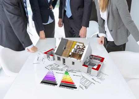 eficiencia: Encuentro con personas alrededor de una mesa con un modelo de arquitectura que muestra el aislamiento de techos y cuadros de eficiencia energ�tica Foto de archivo