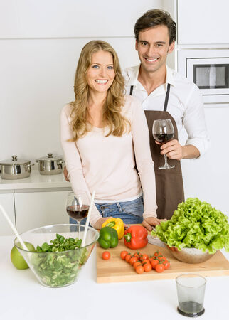 Happy couple fooling around while preparing healthy dinner photo